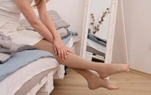Woman sits on bed putting on compression stockings